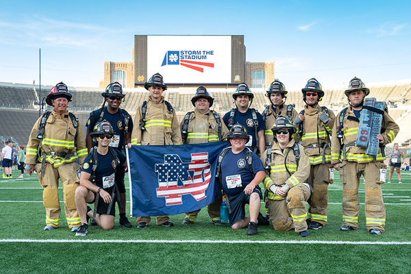 Clay firefighters waive a patriotic Notre Dame flag at