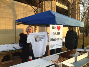 Graduate School and program administrators and staff handing out coffee, cocoa, pastries, and T-shirts to graduate students